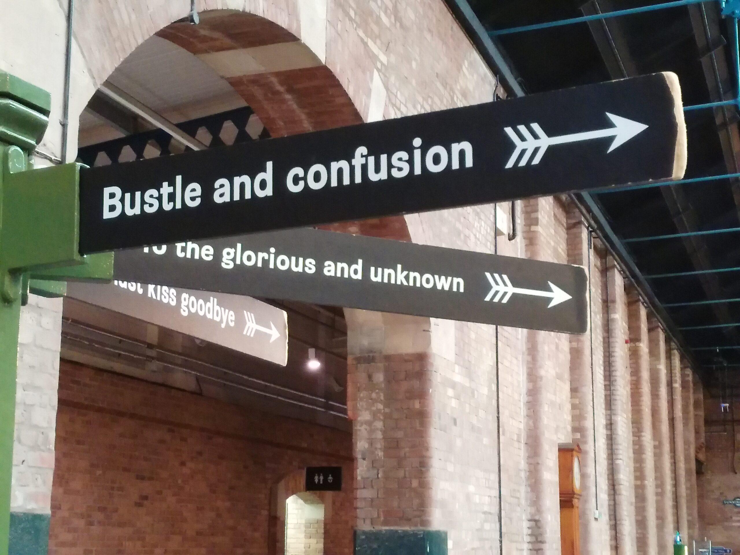 """Vor dem Hintergrund einer Ziegelsteinmauer zeigt das Foto zwei schwarze Hinweisschilder mit weißen Pfeilen, einmal in Richtung """"Bustle and confusion"""", einmal in Richtung """"To the glorious and unknown""""."""