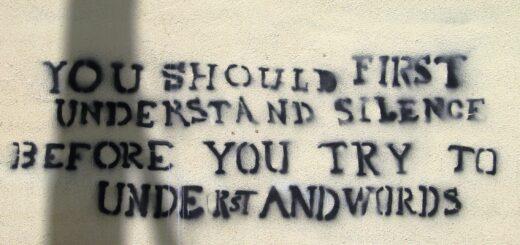 """Schriftzug """"You should first understand silence, before you try to understand words"""" (Du solltest zuerst die Stille verstehen, bevor du versuchst, Worte zu verstehen) in dunkler Schrift auf einer hellen Wand."""