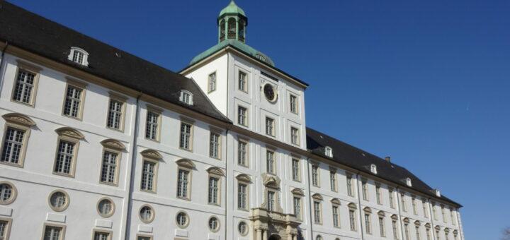 Das Foto zeigt eine Ansicht des barocken Südflügels des Schlosses Gottorf. Das Schloss ist weiß, in der Mitte befindet sich ein Torbogen.