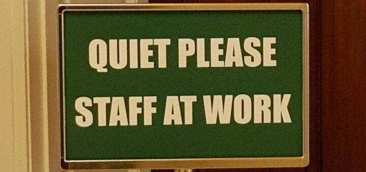 """""""Quiet please. Staff at work"""" steht in weißer Schrift auf dem grünen Schild vor einer Bibliothekstür, also """"Ruhe bitte. Hier wird gearbeitet""""."""