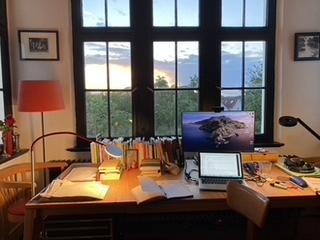 Das Foto zeigt einen Schreibtisch vor einem Fenster, durch das Himmel und Bäume zu sehen sind. Auf dem Schreibtisch befinden sich Bücher, Stifte, Papierstapel, Notizbücher und ein Computer.